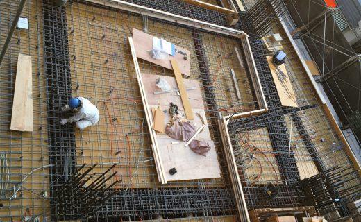 梁貫通スリーブの補強に手間取っている中、型枠の最終建て込みや耐震スリットの差込みの作業が行われている
