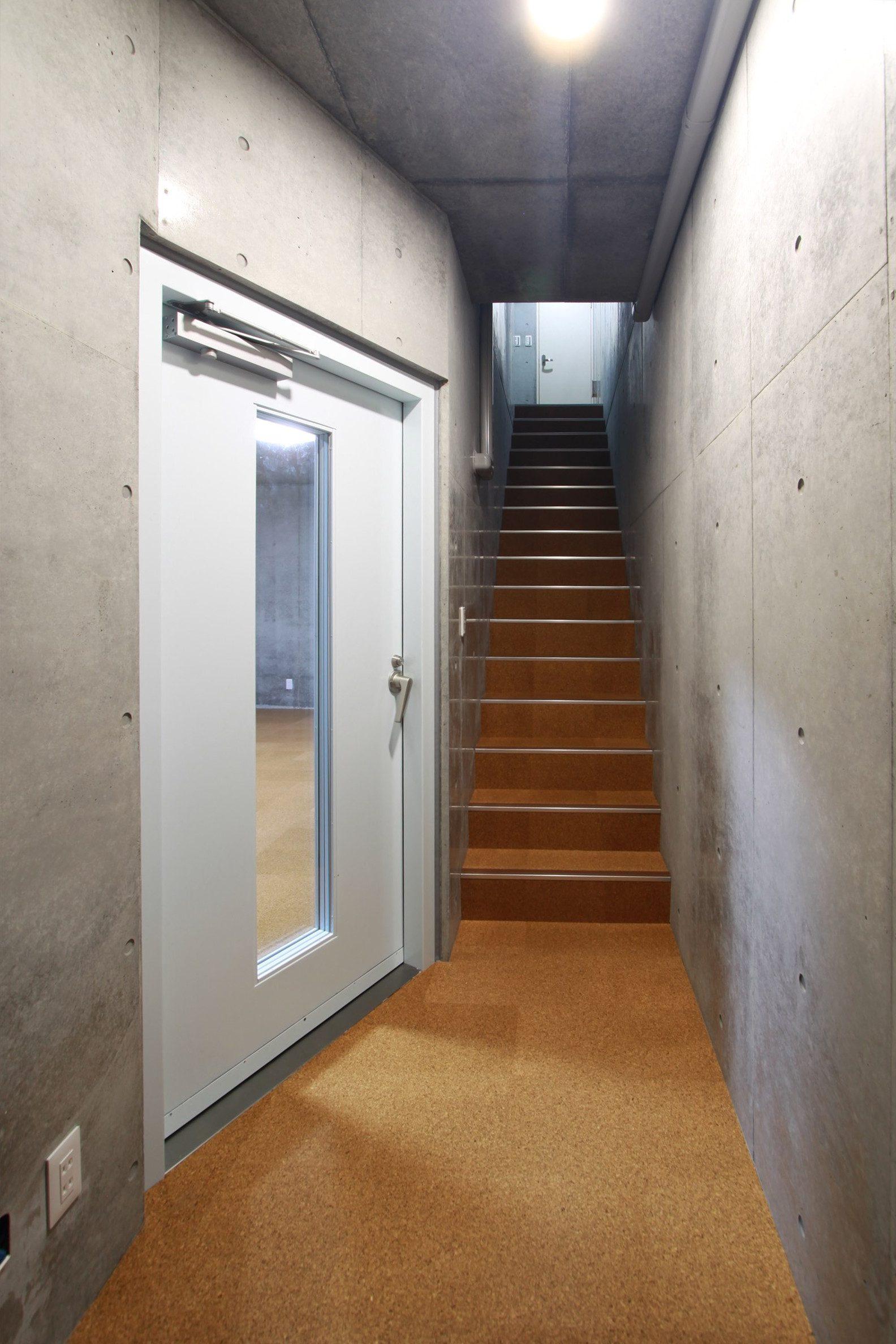 1階の玄関ならびにトイレ前のホールから階段を下りてきて待合スペースとスタジオの入口