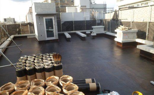 防水工事の場合、下地となる屋上スラブのコンクリート面の平滑化やコンクリート面と防水剤との密着を良くするための密着剤(プライマー:画像黒色塗膜)を先行工事をし、そのプライマーの上に防水剤を重ねていきます。