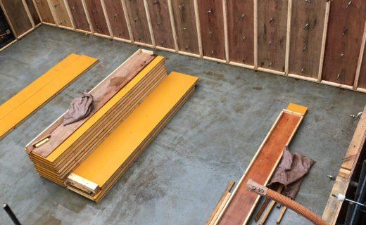 工場で事前に組み立てられた地下室の柱壁型枠が比較的広い部屋に搬入され、敷桟の上に規則正しくそれら内部柱壁型枠を建て込んでいきます
