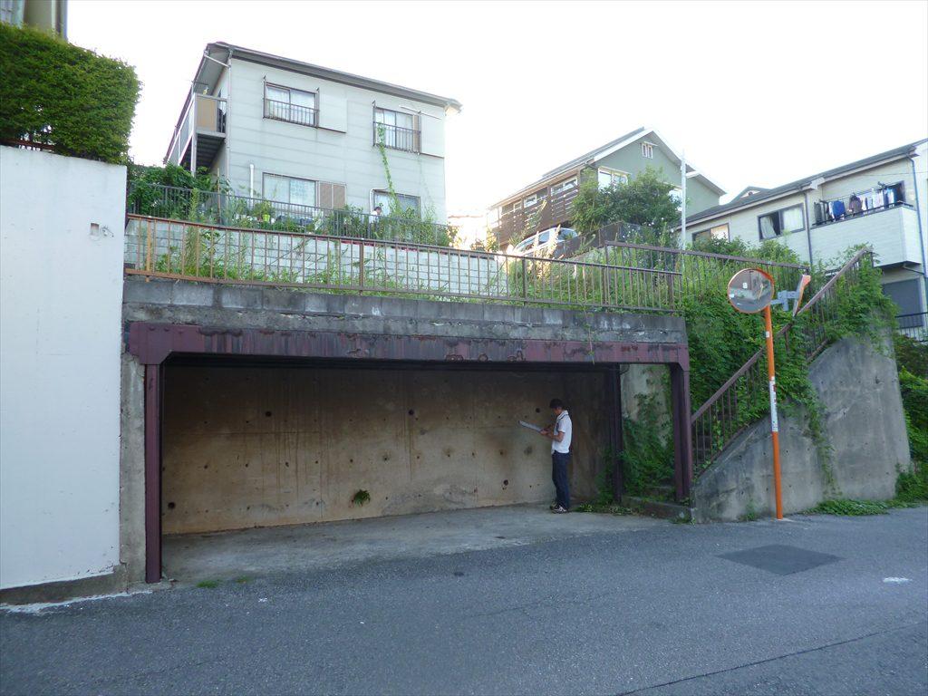 3.5m高のコンクリート擁壁付の土地の左側には鉄骨造の人工地盤の車庫スペースがあり、その敷地のさらに上には3.5m擁壁付の隣地があります
