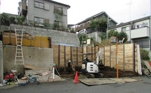3.5mの擁壁の一部を解体して掘削を先行しながら平地を作り地盤補強杭を貫入します。さらに掘り進んで整地を行い重機を入れて山留杭打設してさらに掘削して道路レベル-50cmの杭頭を露出して掘削を完了します