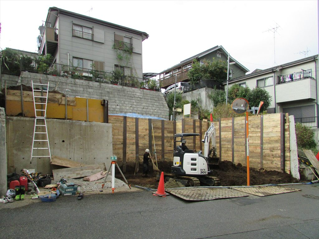 3.5mの擁壁の一部を解体して掘り進んでいき重機を敷地の中に入れて山留を行いさらに掘削していく